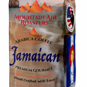 one pound mountain air roasters, jamaican coffee bag. the beach with sand, the ocean with small rustling waves in an isolated cove with pink and purple clouds of evening sunlight