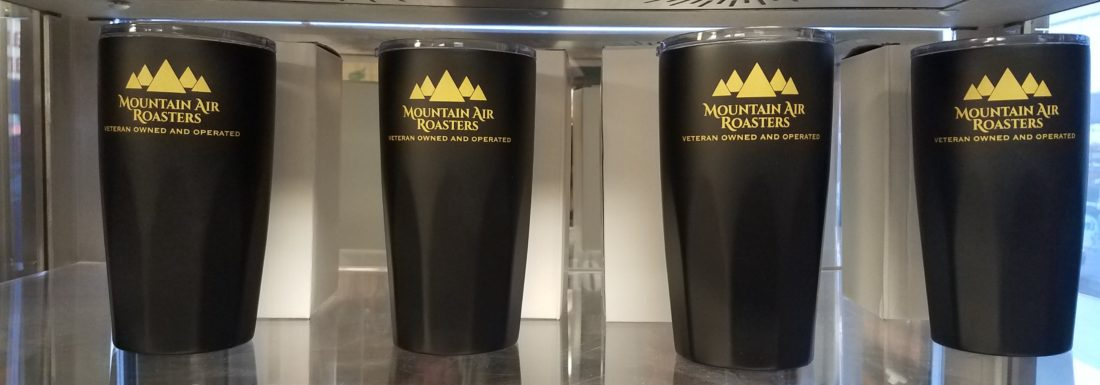 four coffee tumblers on a shelf side by side black 20oz cups with lids and a mountain air roasters logo