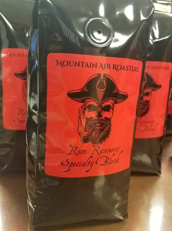 Mountain Air Roasters Rum Runners Specialty blend, black bag, big red sticker and a black pirate skull with pirate captains hat smoking an old cob pipe