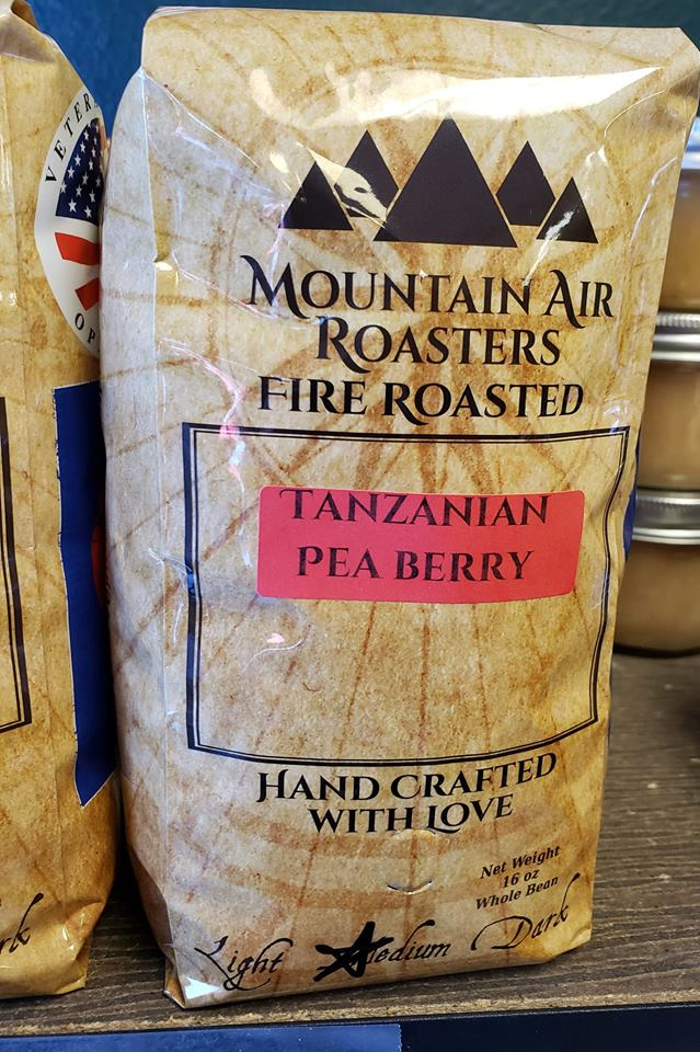 Mountain Air Roasters Fire Roasted coffee bag with a nautical compass on it, with a Tanzanian Pea Berry sticker on the bag